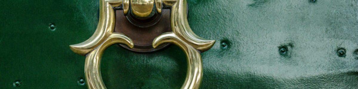 Beautiful metal handle on a green front door. Close-up.